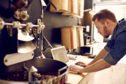 Coffee Roaster looking at automated order system on his laptop